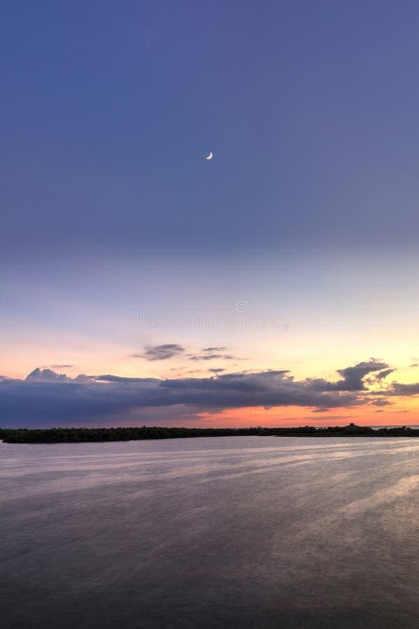 Luna creciente sobre nuevo paso de la puesta del sol de la bahía de Estero en Bonita Spr fotos de archivo