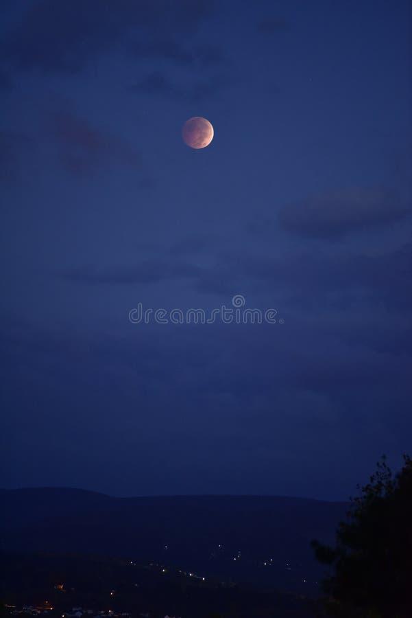 Luna de la sangre con las luces de la ciudad imagenes de archivo