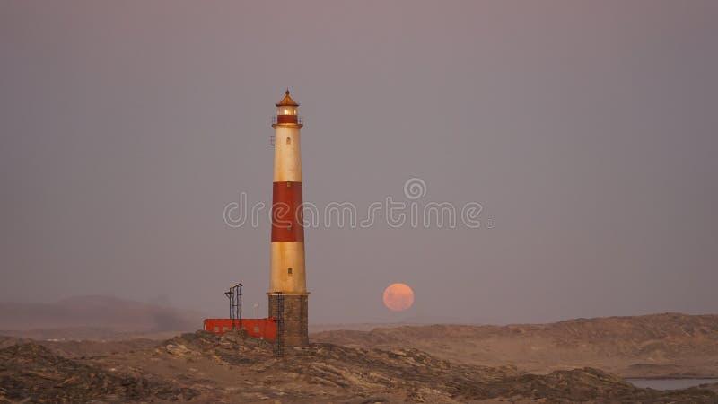 Luna de la sangre que sube en el faro de Luederitz en el punto de Díaz cerca del deritz del ¼ de LÃ, Namibia, África fotografía de archivo