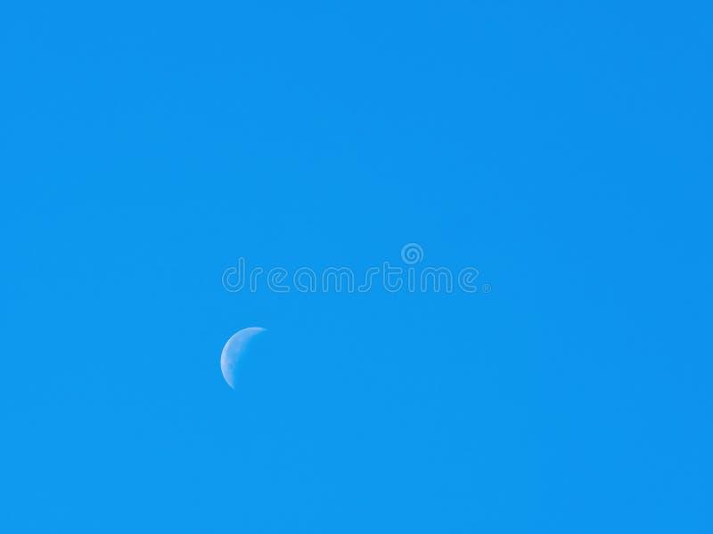 Luna durante il giorno con cielo blu fotografie stock