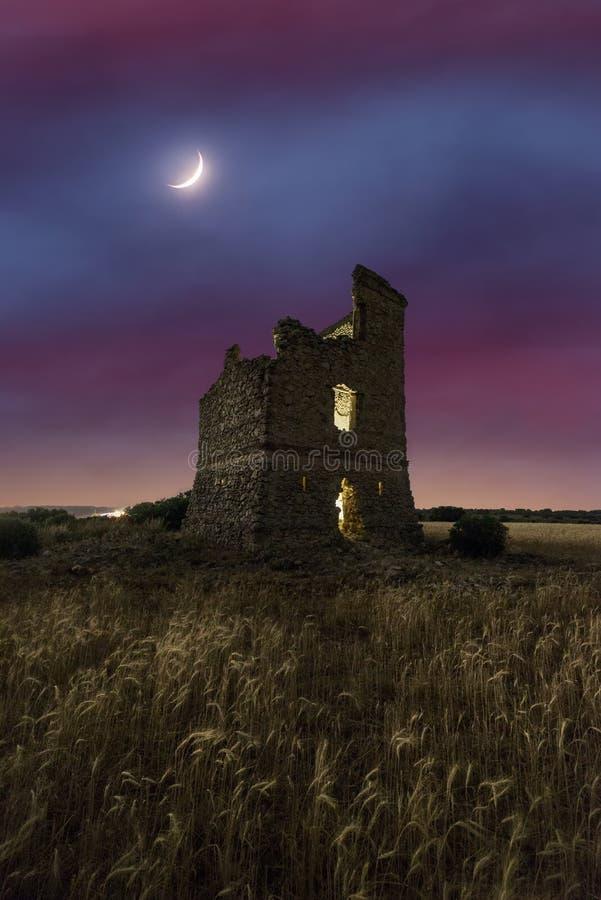 Luna en un crepúsculo sobre las ruinas de un castillo viejo imagenes de archivo
