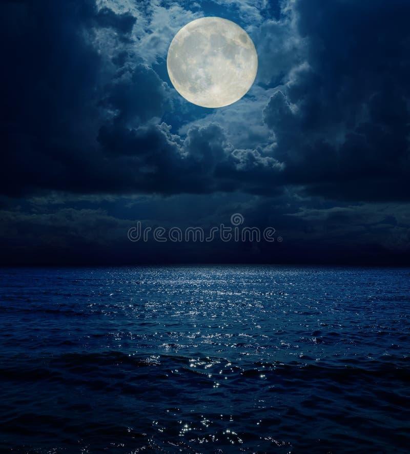 Luna estupenda en nubes oscuras sobre el mar fotos de archivo libres de regalías