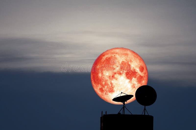 Luna llena de los pescados detrás en antena parabólica de la silueta en el cielo nocturno foto de archivo