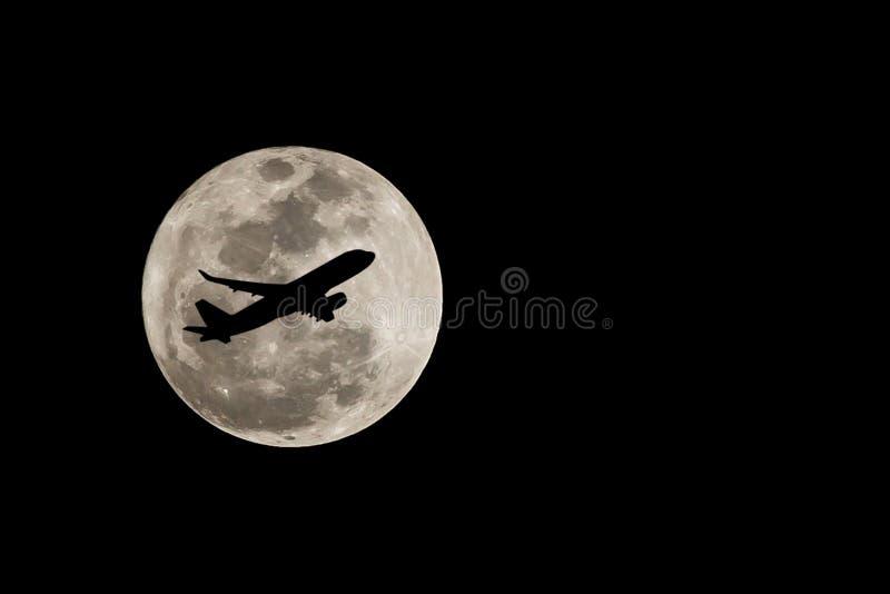 Luna Llena estupenda sobre Tailandia y la silueta del aeroplano en Nove imágenes de archivo libres de regalías