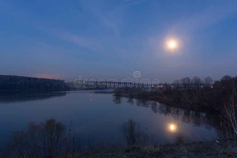 Luna Llena grande en el cielo azul sobre el lago en la noche foto de archivo