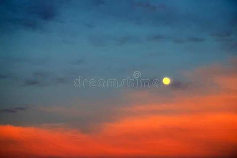 Luna Llena pintoresca en un fondo de nubes azules y rojas hermosas Nubes en la puesta del sol, salida del sol en la Luna Llena imagenes de archivo