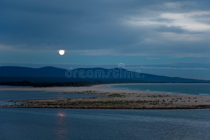 Luna Llena que se levanta sobre paisaje del lago y del mar en la oscuridad imagen de archivo