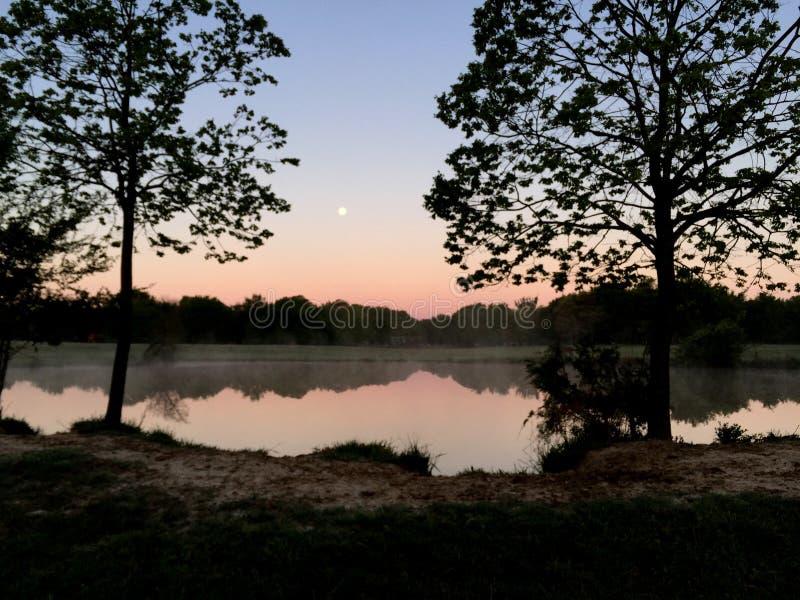 Luna Llena reflejada en el lago en el amanecer imagenes de archivo