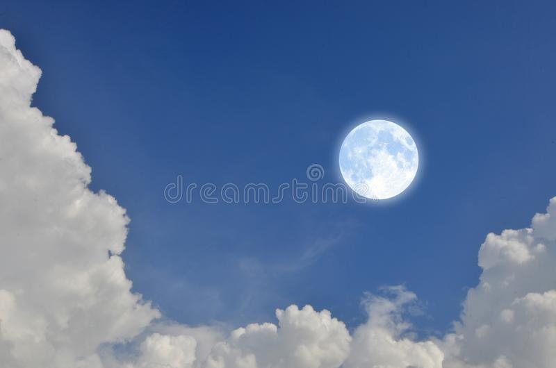 Luna Llena romántica y encantadora en cielo azul con las nubes blancas imagen de archivo