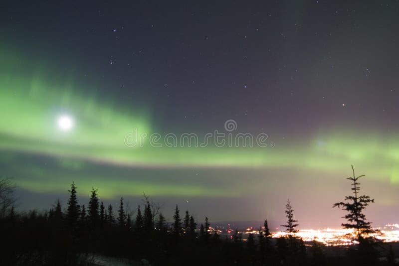 Luna Llena y aurora colorida activa sobre Fairbanks Alaska foto de archivo