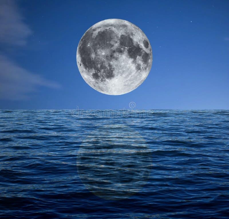 Luna piena alla notte sopra il mare fotografie stock