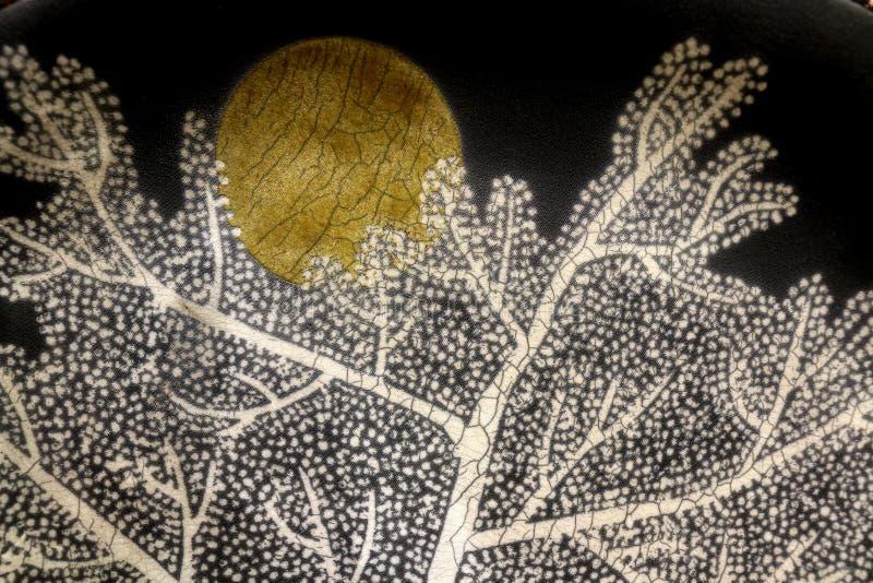 Luna piena in aumento dietro l'albero fotografia stock