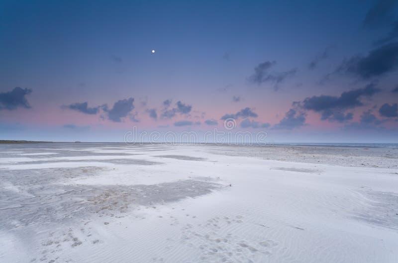 Luna piena e cielo di alba sopra la spiaggia di sabbia fotografia stock libera da diritti