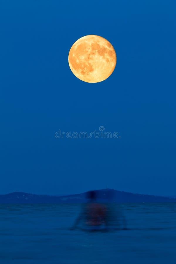 Luna piena sopra il lago sulla spiaggia fotografia stock