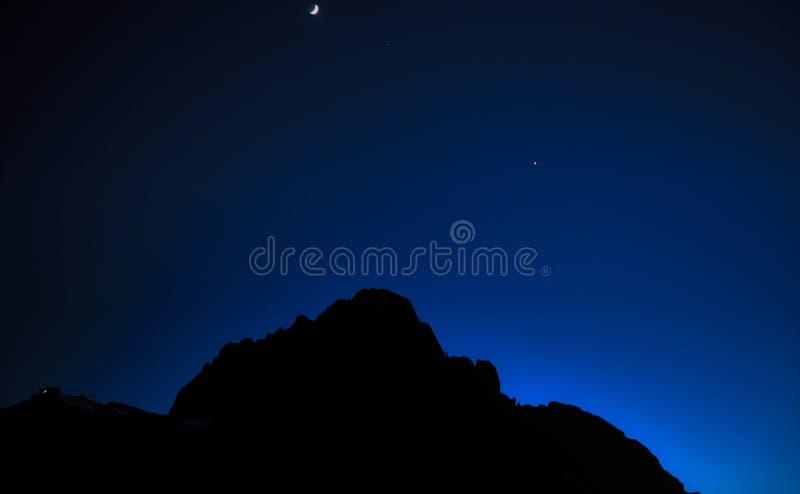 Luna sopra le montagne la sera d'inverno fotografia stock libera da diritti