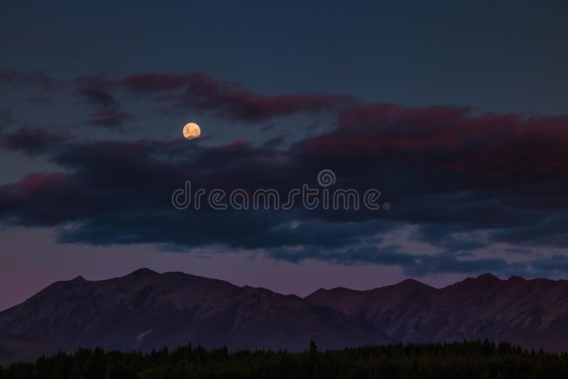 Luna sopra le montagne nella notte fotografia stock libera da diritti