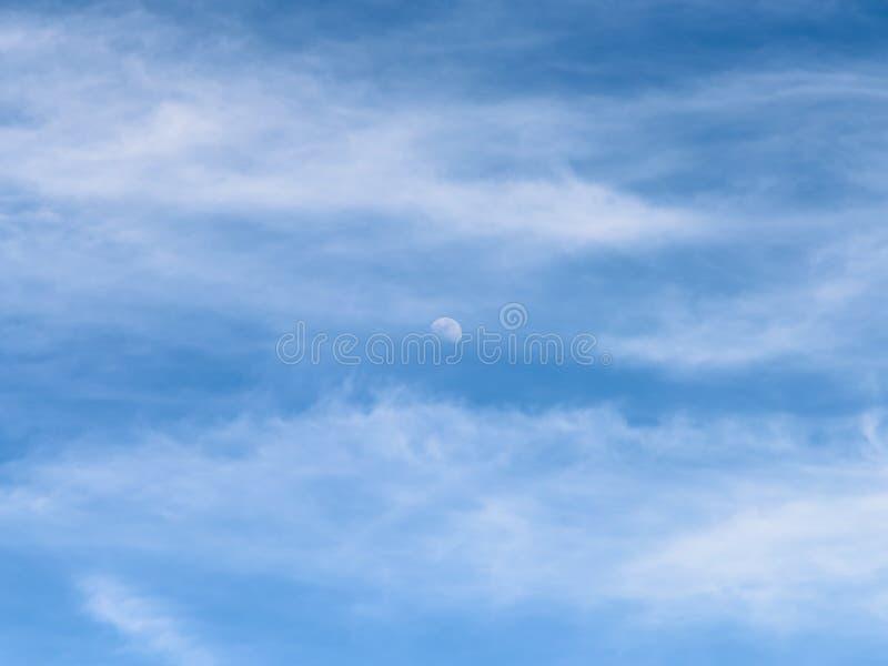 Luna visible en cielo azul de luz del día con las nubes blancas foto de archivo libre de regalías