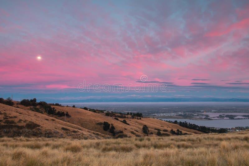 Luna vista en salida del sol rosada sobre ciudad imagen de archivo libre de regalías