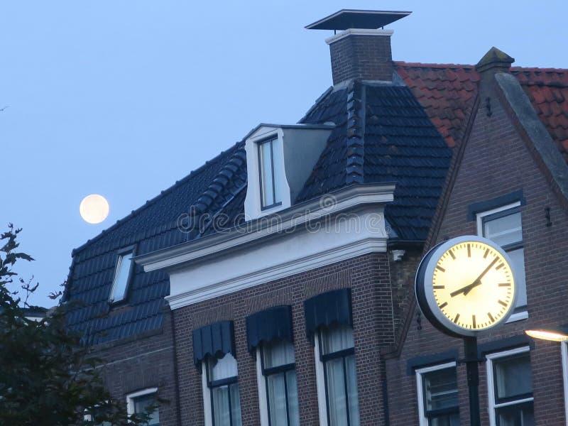 Luna y reloj que juegan dobles en el reloj de ocho o por la mañana imagenes de archivo