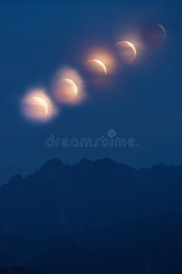 Lunar eclipse over the High Tatra mountains. Time series image. Of the beautiful natural phenomenon, vertical background royalty free stock photo