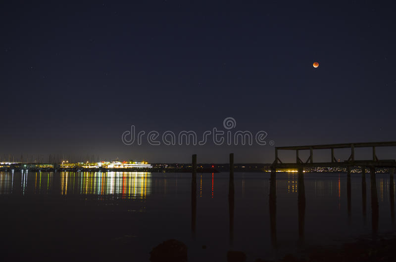 Lunar eclipse of super moon and ferry dock at night. Super moon lunar eclipse, old pier and the Washington state ferry terminal in Kingston stock images