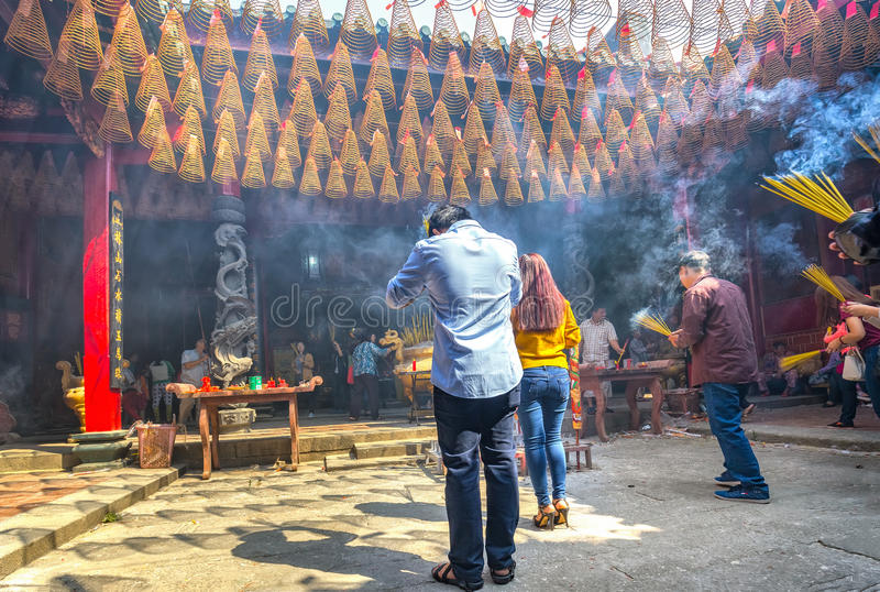 Lunar New Year Day attend temple. Ho Chi Minh City, Vietnam - February 8th, 2016: The man clasped hands in prayer with a bunch of incense on hand last top stock photography