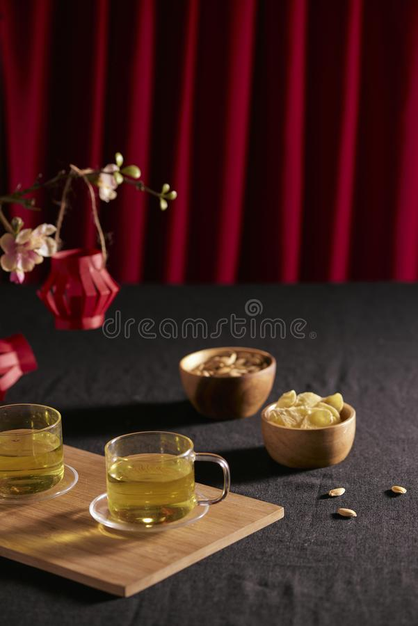 Lunar new year food and drink still life on black background. Translation of text paper in image: Prosperity.  stock photos