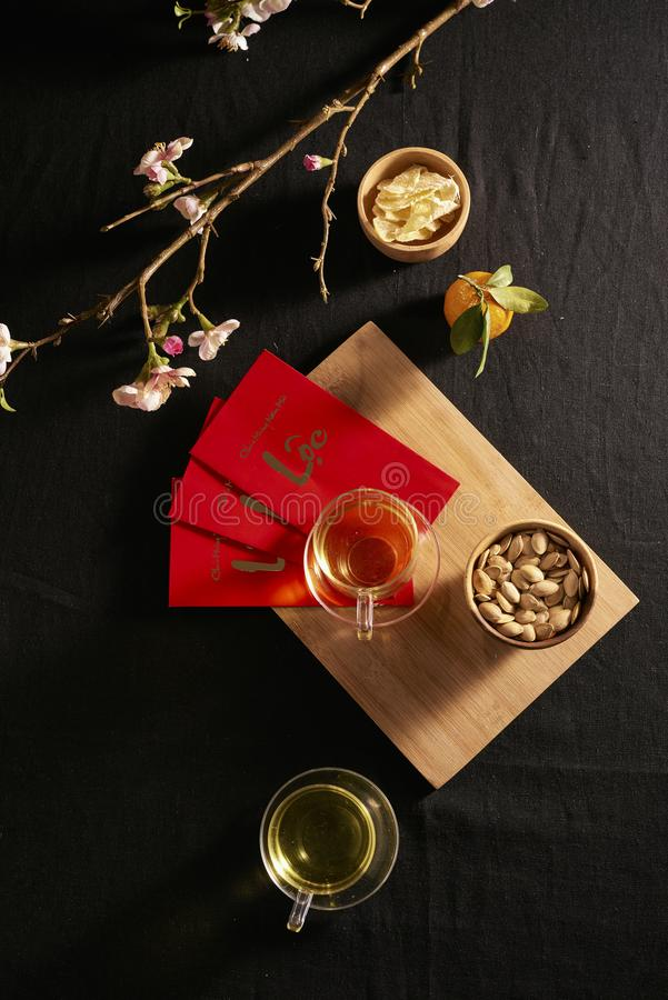 Lunar new year food and drink still life on black background. Translation of text paper in image: Prosperity.  royalty free stock photo