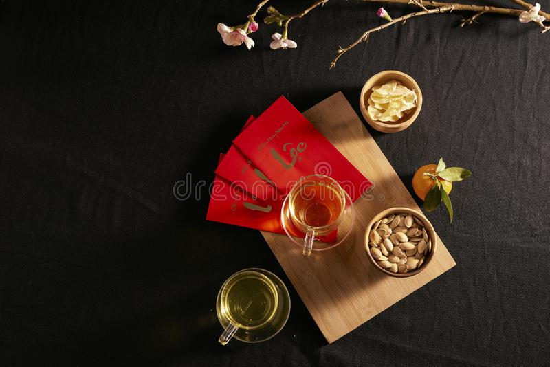 Lunar new year food and drink still life on black background. Translation of text paper in image: Prosperity.  stock image