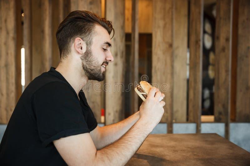 Lunch bij de koffie Een jonge kerel bekijkt de hamburger en wil gaan zitten royalty-vrije stock foto