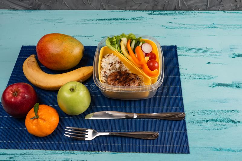 Lunch box with appetizing food and on light wooden table. Copy space stock images