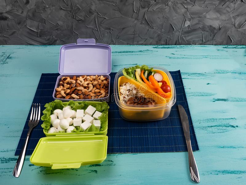 Lunch box with appetizing food and on light wooden table. Copy space stock photos