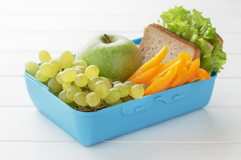 Lunch box filled healthy fresh food on white wooden table. royalty free stock photo