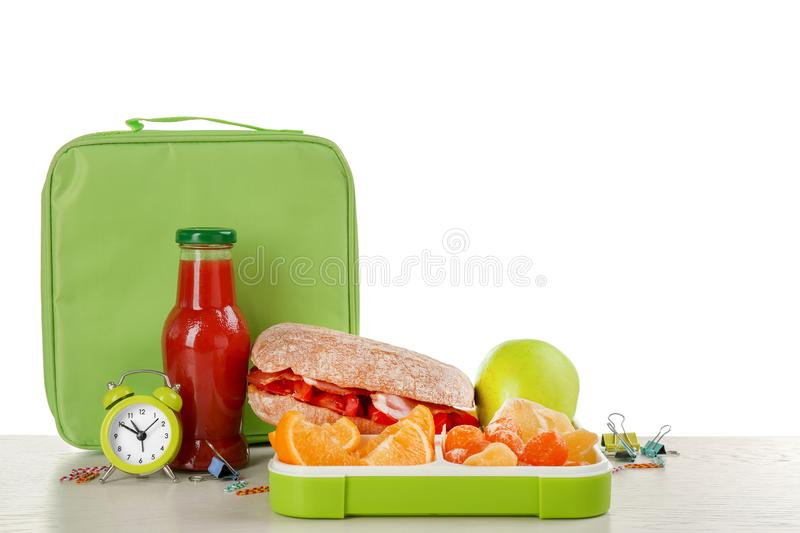Lunch box with food and bag on table against white background. Lunch box with appetizing food and bag on table against white background stock photos