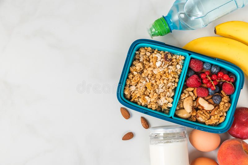 Lunch box with food ready to go for work or school. healthy breakfast with granola, nuts, berries and yogur stock photography
