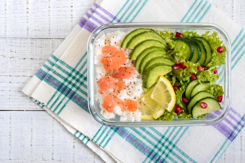 Lunch box: rice, salmon, salad with cucumber, avocado, greens on a white wooden background. Fitness food. The concept of healthy eating. School lunch box stock photo