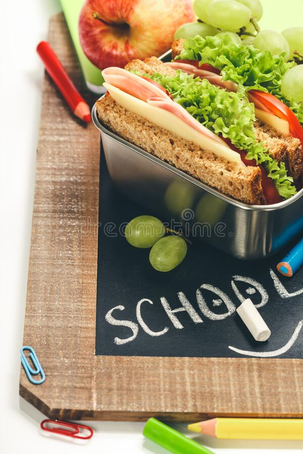 Lunch box with sandwich and fruits on chalk board stock images