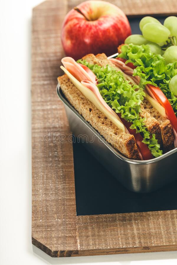 Lunch box with sandwich and fruits on chalk board stock image
