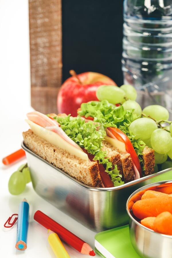 Lunch box with sandwich and fruits infront of chalk board, royalty free stock image