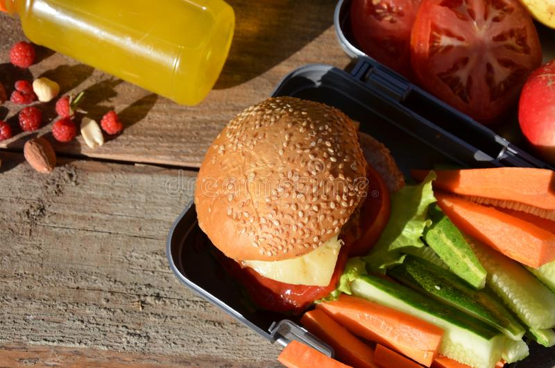 Lunch boxes with food ready to go for work or school, meal preparation or dieting concept. Hamburgers with lettuce. Yellow orange juice. with banana nuts royalty free stock photos