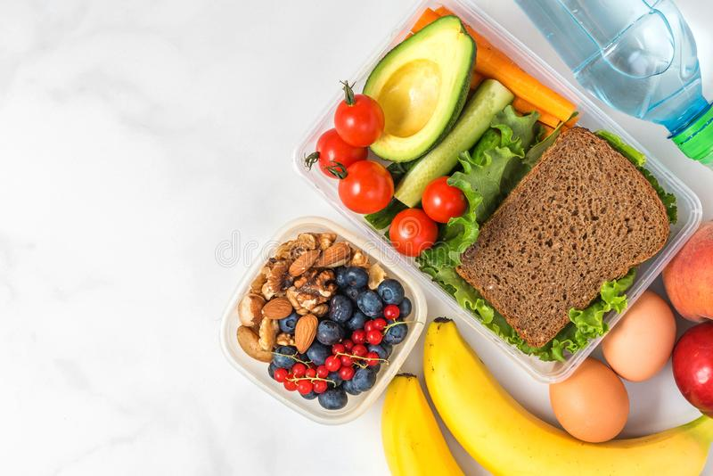 Lunch boxes with food ready to go for work or school. sandwich, vegetables, avocado, nuts, berries, eggs and water royalty free stock photo