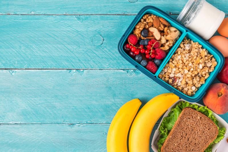 Lunch boxes with food ready to go for work or school. sandwich, vegetables, nuts, berries, eggs and yogurt royalty free stock photo