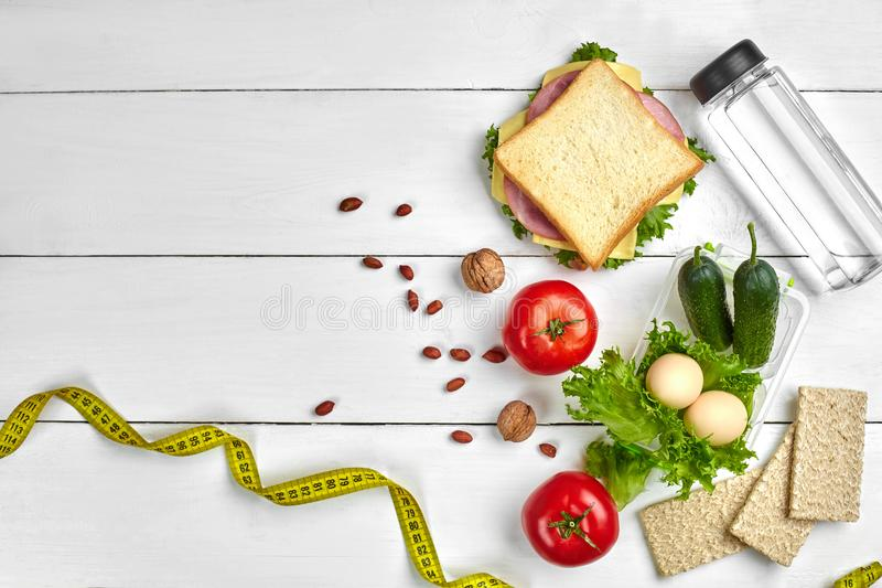 Lunch boxes with sandwich and fresh vegetables, bottle of water, nuts and eggs on white wooden background. Top view with royalty free stock image