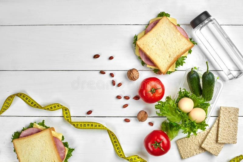 Lunch boxes with sandwiches and fresh vegetables, bottle of water, nuts and eggs on white wooden background. Top view. Lunch boxes with sandwiches and fresh royalty free stock images