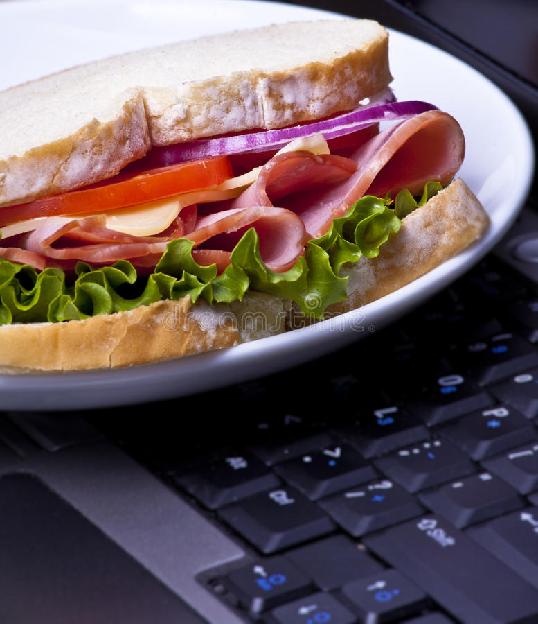 Lunch break. A plate with a sandwich on an laptop lunch break - concept royalty free stock images