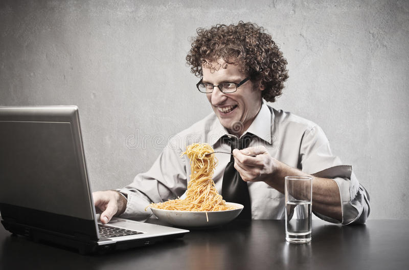 Lunch Break. Businessman eating spaghetti while using a laptop computer stock photos