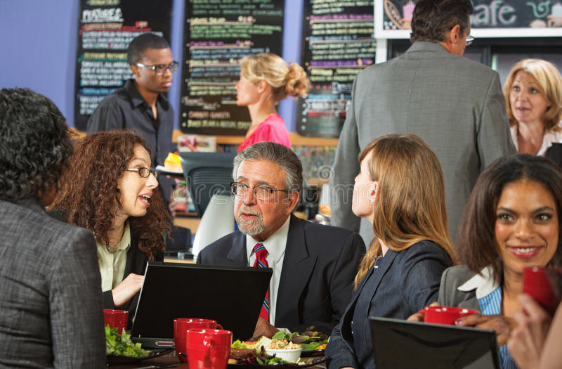 Lunch Break with Workers. White collar workers with laptop in cafeteria royalty free stock photography