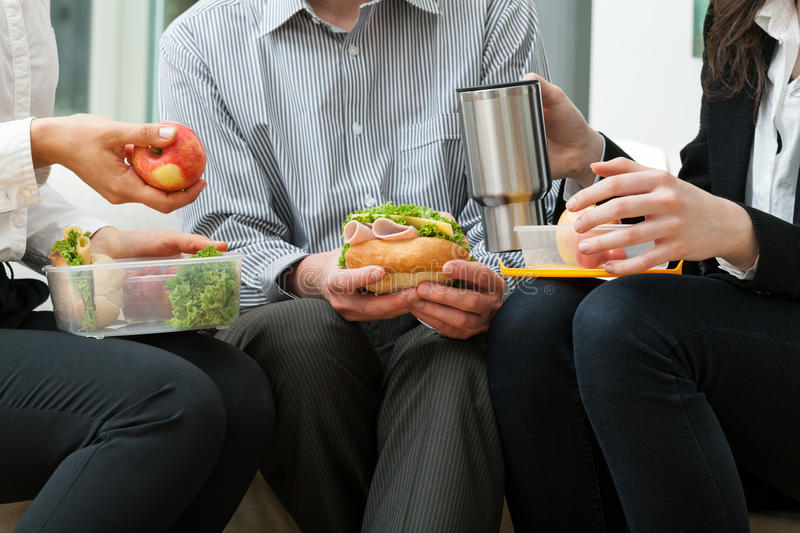 Lunch break. Young businessmen eating homemade lunch during break stock image