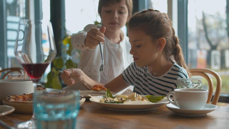 Mother and son takes cheese from a plate, girl eat pizza stock image