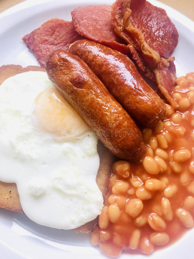Full English breakfast. With fried egg, bacon, sausages, fried bread with baked beans served on a white plate stock photo